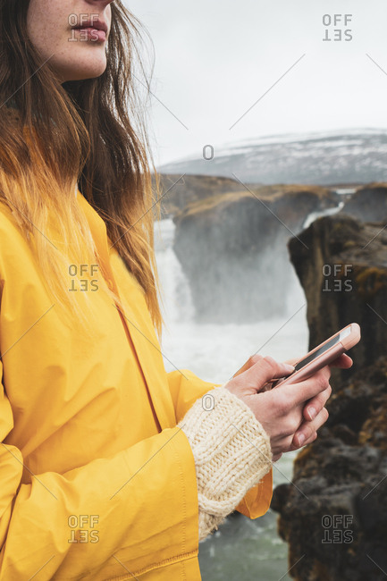 Iceland- woman with cell phone at Godafoss waterfall