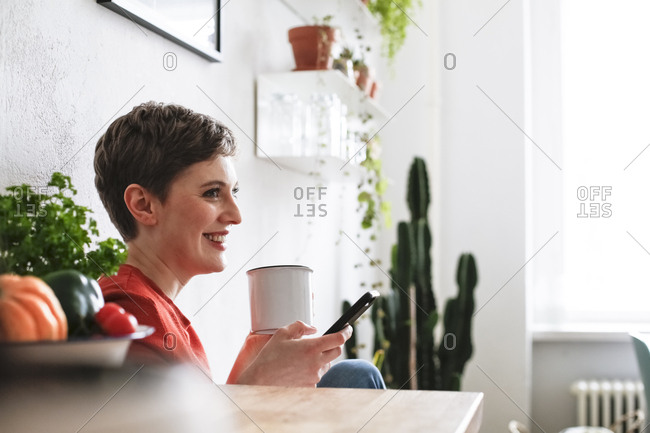Woman sitting in kitchen- drinking coffee and checking smartphone messages