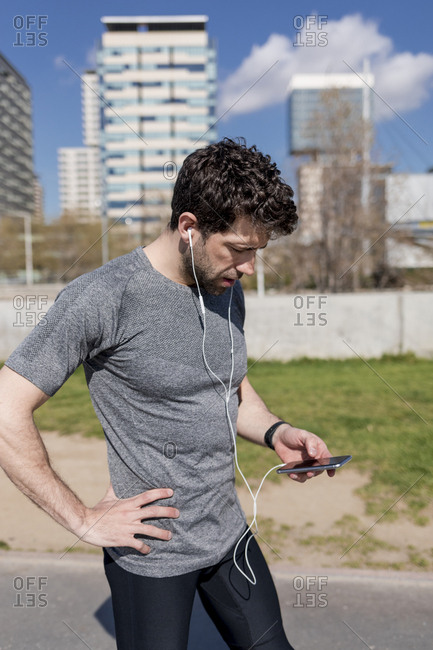 Sportive man with cell phone and earphones in urban area