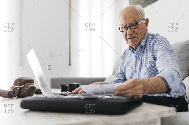 Senior man working with a computer and his old photo cameras and old photos