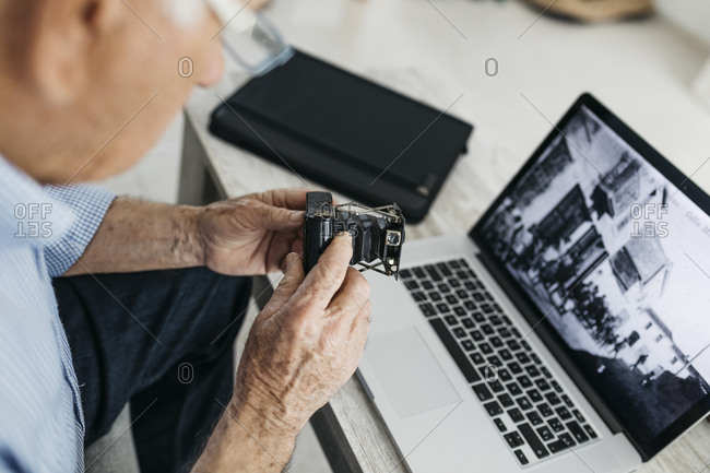 Senior man using laptop and holding his old photo camera- screen with old photo