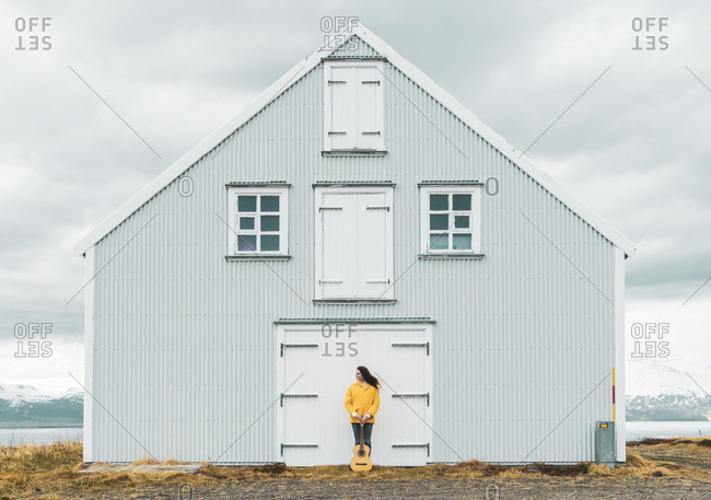 Iceland- woman with guitar standing at lonely house