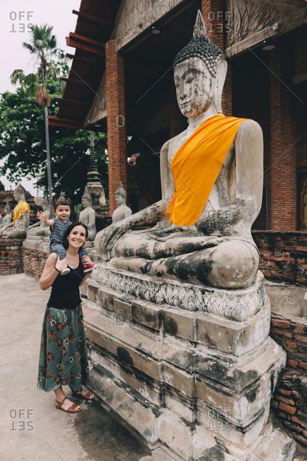 Thailand- Ayutthaya- mother and little daughter standing besides Buddha statue at Wat Yai Chaya Mongkhon