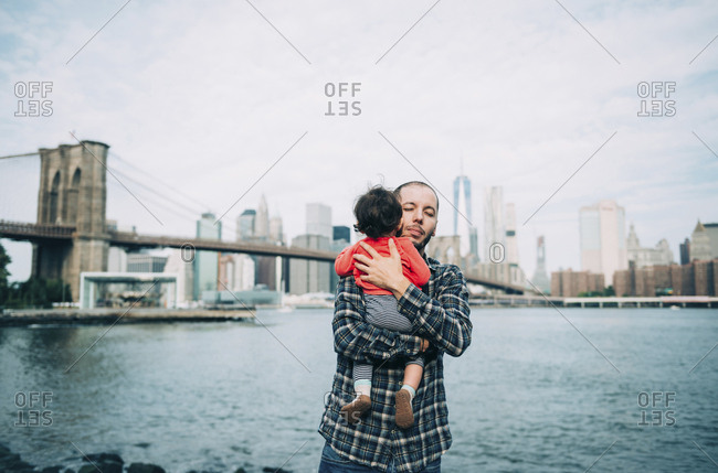 USA- New York- New York City- Father hugging a baby in Brooklyn with Brooklyn Bridge and Manhattan in the background