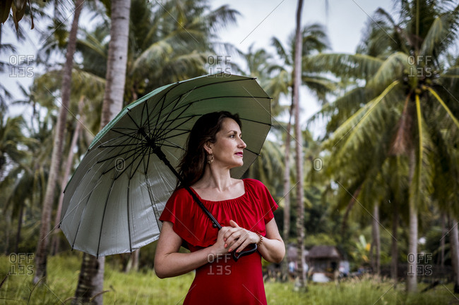 Thailand- Koh Phangan- portrait of woman strolling with umbrella