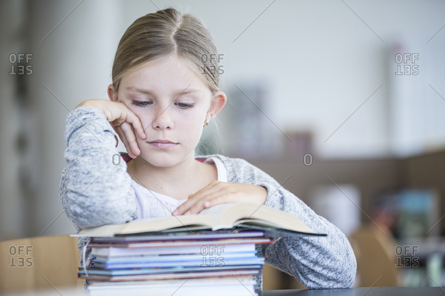 Schoolgirl reading book on table in school