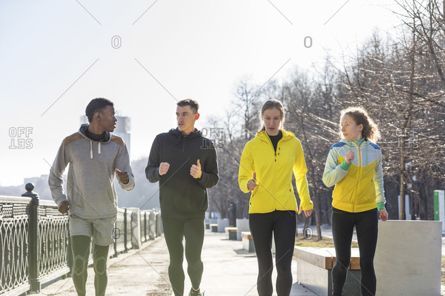 Friends running on promenade in the city