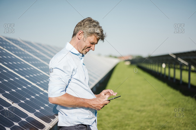 Businessman using tablet at solar park