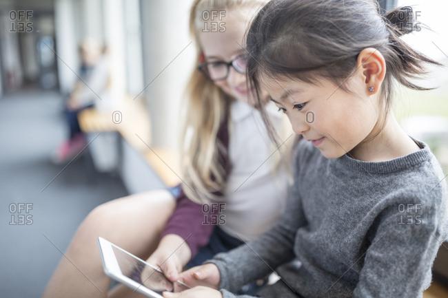 Schoolgirls sharing a tablet on school corridor