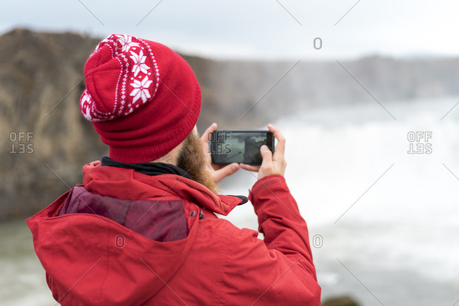 Iceland- North of Iceland- young man photographing waterfall