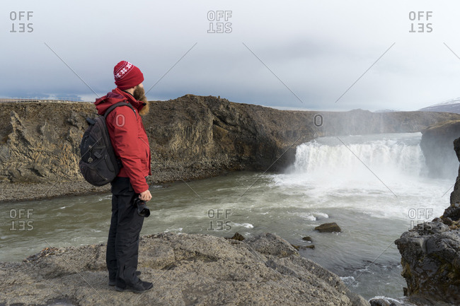 Iceland- North of Iceland- young man looking to waterfall