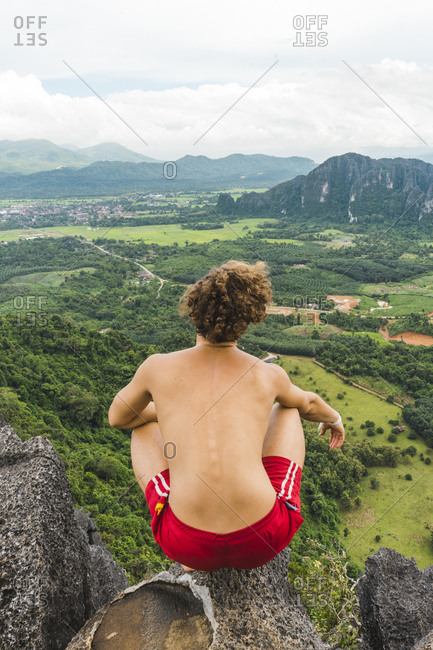 Laos- Vang Vieng- young man on top of rocks overlooking landscape of rice fields