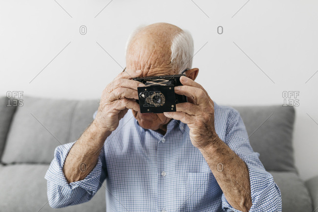 Senior man taking a photo with an old photo camera