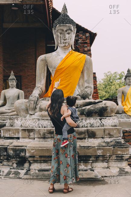 Thailand- Ayutthaya- back view of mother and little daughter visiting Wat Yai Chaya Mongkhon