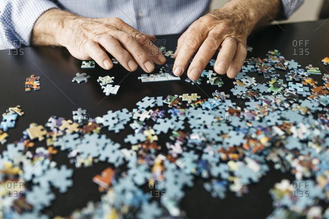 Senior man doing a jigsaw