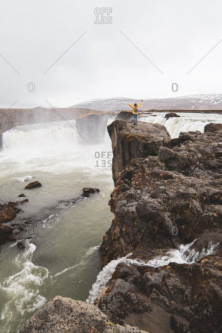 Iceland- woman standing at Godafoss waterfall with raised arms