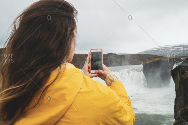 Iceland- woman taking cell phone picture of Godafoss waterfall