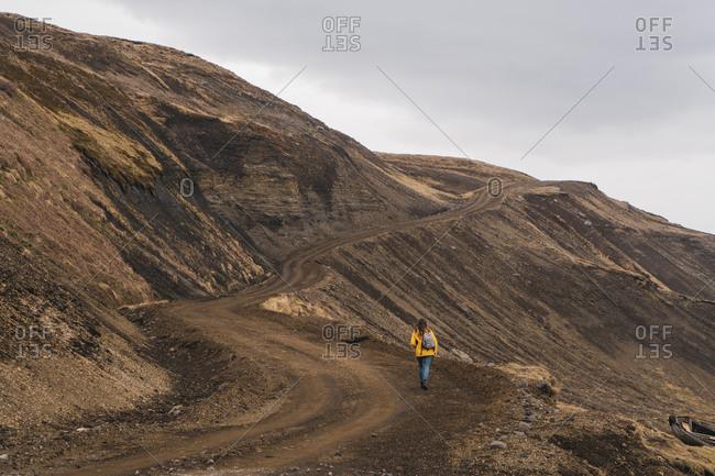 Iceland- woman walking in deserted landscape