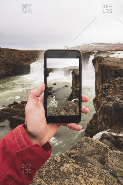 Iceland- hand holding cell phone with picture of Godafoss waterfall