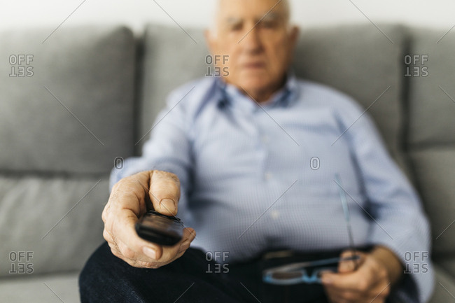 Senior man watching TV from the couch at home- focused on hand
