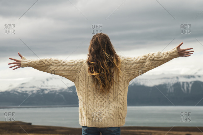 Iceland- woman standing at lakeside with outstretched arms