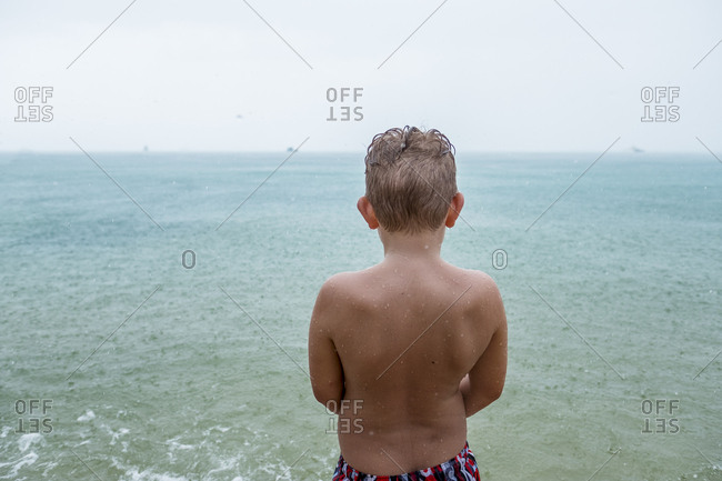 Back view of boy standing in front of the sea on rainy day