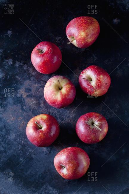 Seven red apples on dark ground