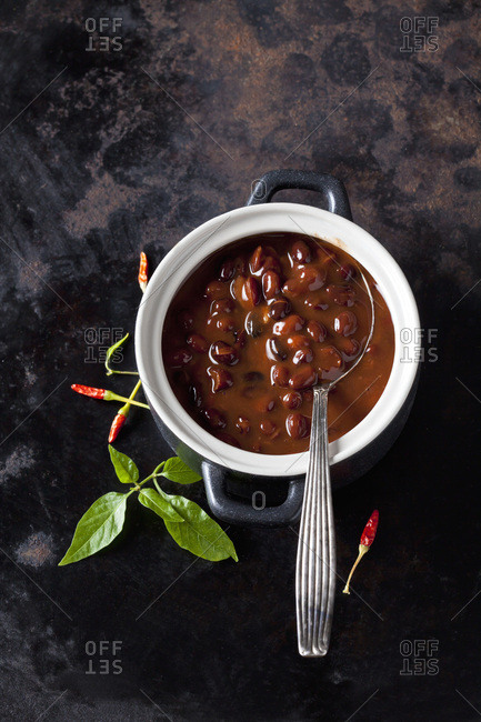Tureen of black bean soup with chili pepper