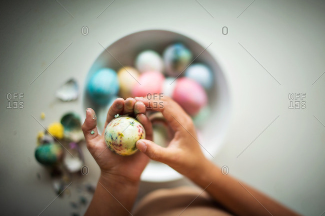 Child's hand peeling dyed Easter eggs