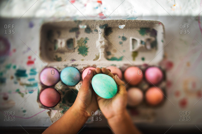 Child's hand holding dyed Easter eggs