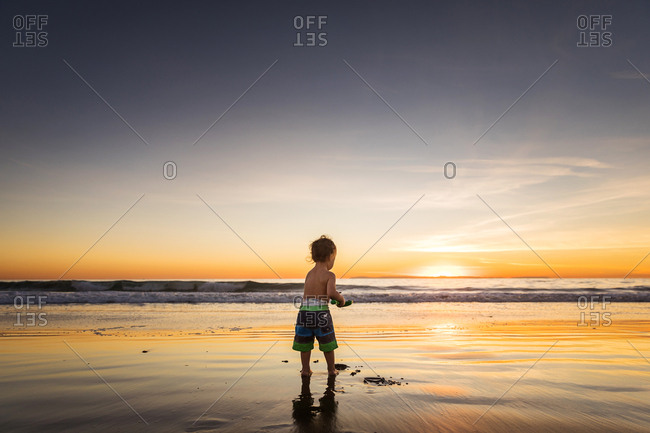 Child playing on a beach at sunset