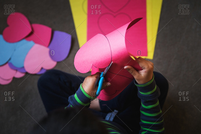 Child cutting hearts into construction paper