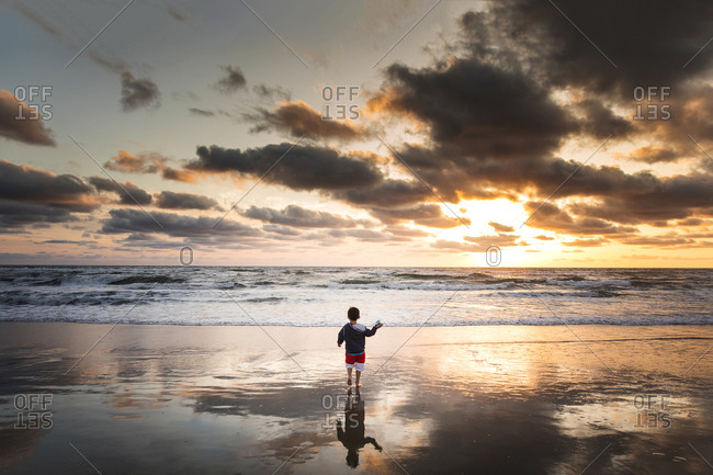 Boy playing on a beach at sunset