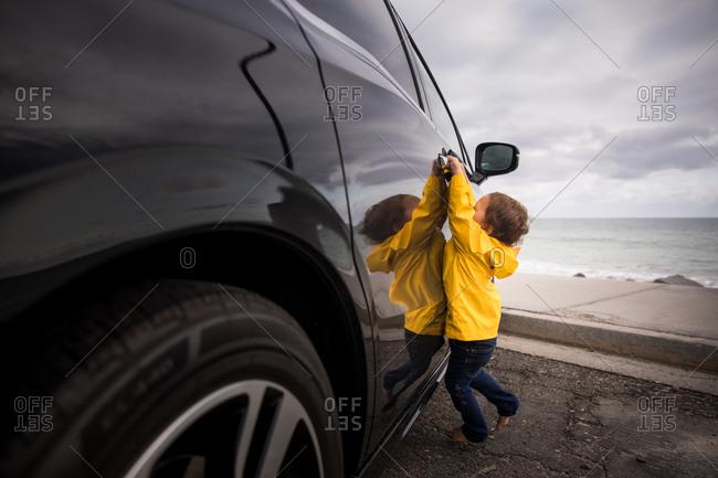 Child trying to open car door by the ocean