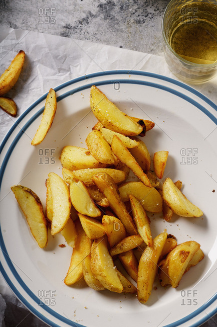 Fried spicy garlic potato wedges served on a plate