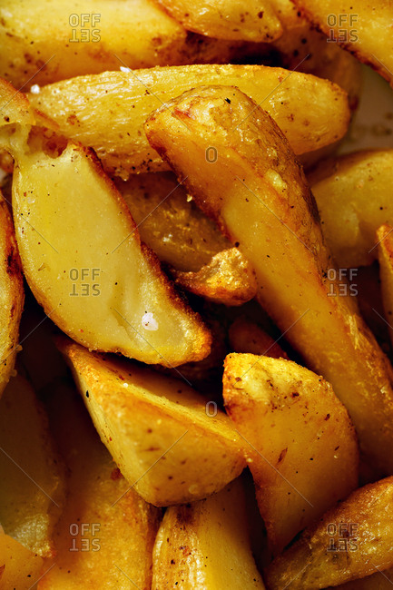 Close up image of fried spicy garlic potato wedges on a plate