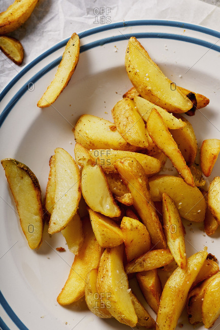 Fried spicy garlic potato wedges on a plate