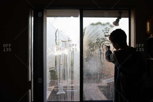 Rearview of boy drawing faces on condensation of window