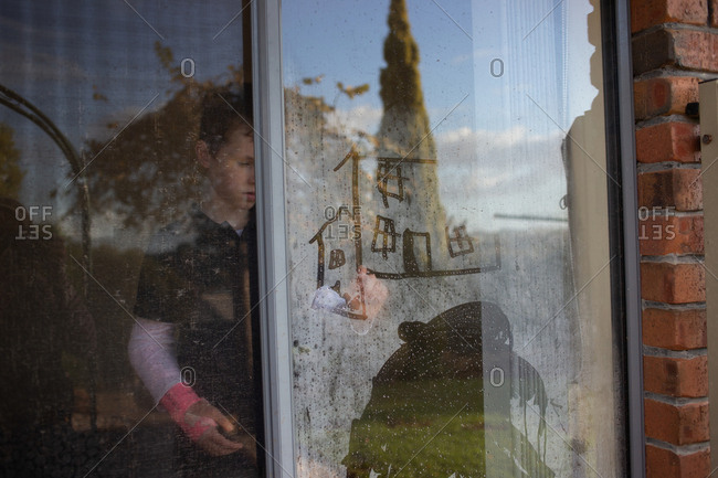 View from outside of boy with arm in plaster drawing on condensation on windows
