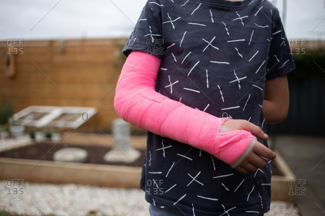Cropped view of young boy's arm wrapped in pink plaster cast