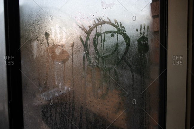 Faces and hand prints in condensation on window