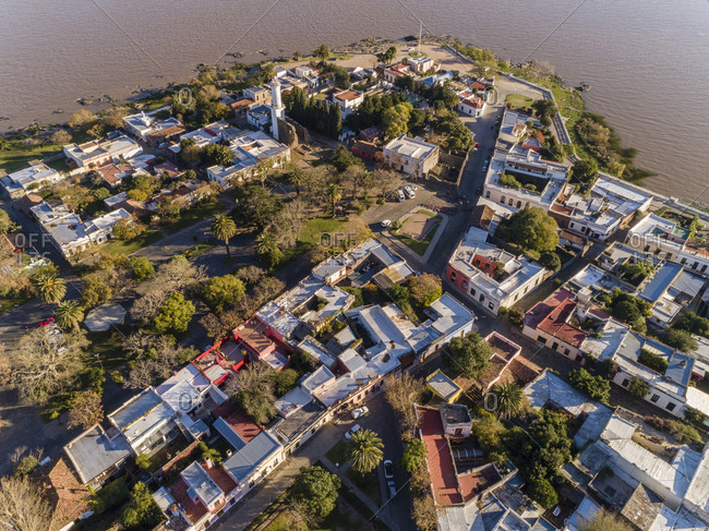 Drone's eye view of neighborhood by the river at sunset in Colonia del Sacramento, Uruguay