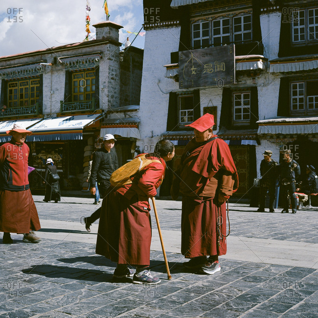 Lhasa, Tibet - April 21, 2018: Two monks greeting each other on lively Barkhor Street