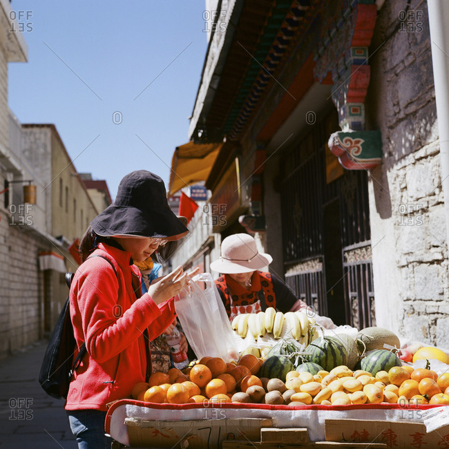 Lhasa, Tibet - April 21, 2018: Local woman purchasing oranges on the street