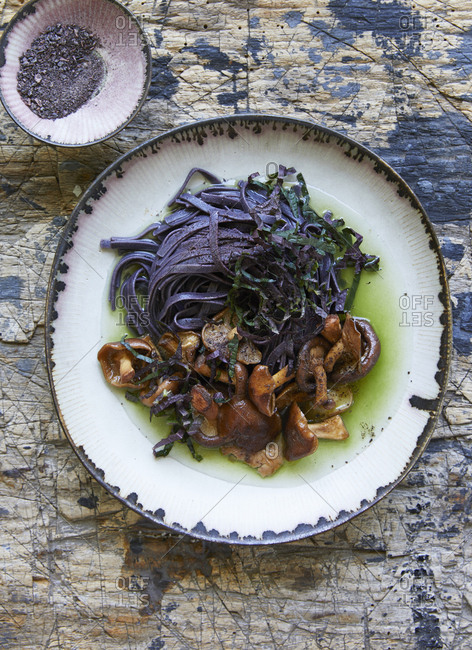 Purple fettuccine and roasted mushrooms served in a black rice matcha broth