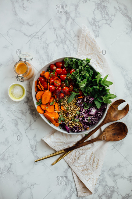Salad in bowl with dressing and serving utensils