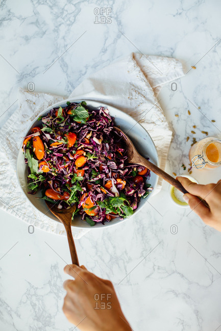 Hands mixing salad in bowl