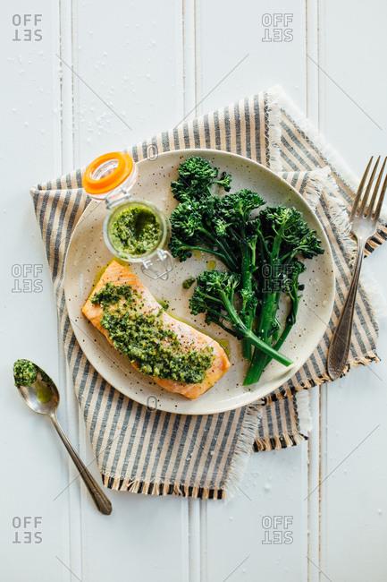Salmon with pesto and broccoli on plate
