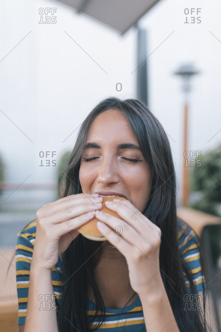 Young woman taking a bite of a burger