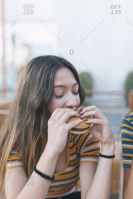 Young woman taking a bite of a hamburger
